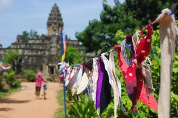 Tissus bouddhistes étendus devant une femme avec son vélo et un temple Khmer près de Angkor