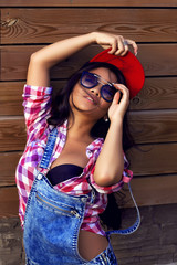 Beautiful asian woman  blue jeans, sunglasses and cap poses in