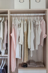 clothes hanging in wooden wardrobe