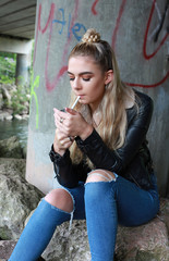 tough looking teenage girl with her nose pierced smoking