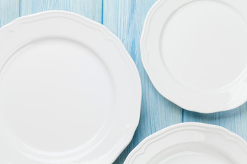 Empty plates over wooden table