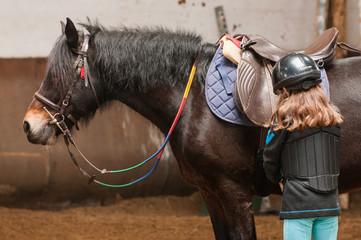 Une petite fille prépare son poney avant de monter dessus
