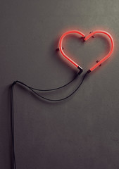 3 D render of an heart shaped neon light against concrete wall. Neon light is turned on and it is glowing in bright red color.