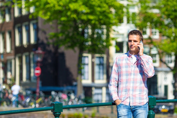 Young caucasian man talking by cell phone on bridge in european