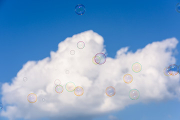 A bunch of colorful soap bubbles flying up into the dark blue sky