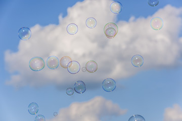 A bunch of colorful soap bubbles flying up into the blue, cloudy sky