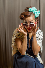 Pretty female wearing sunshades and retro style