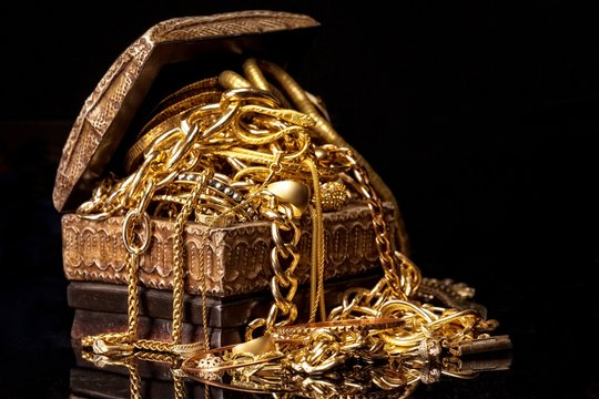 Old wooden chest with pile of various golden jewelry, isolated against black background.