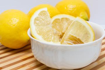 Quartered lemon in white bowl