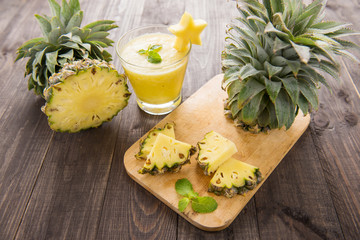 Fresh pineapple with pineapple smoothie on wooden table