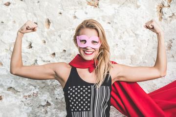 Young woman posing as superhero or superwoman
