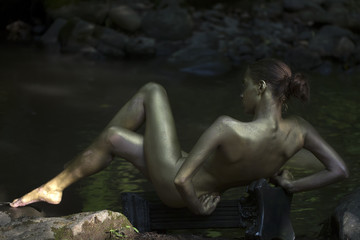 Gold woman near water