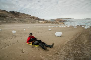 Homme allongé sur une plage au Groenland à côté de glaçons