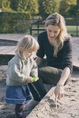 Mother helping daughter make shapes in sandpit