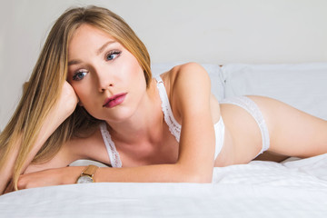 Sexy girl in white lace underwear lying on the bed, emotive, melancholic