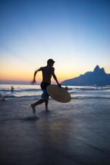 Sunset silhouette of carioca Brazilian running with skimboard on Ipanema Beach Rio de Janeiro Brazil