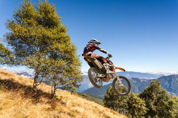 Fototapete - salto con moto da cross in alta montagna