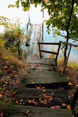 old wooden bridge to the lake in the fall during leaf fall