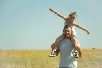 happy father with a daughter on his shoulders in the middle of