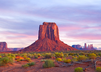 Monument Valley in Utah and Arizona, sunrise or sunset with dramatic clouds, desert landscape of Navajo Nation Park is a famous travel destination for it's red rock formations
