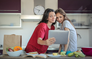 Girls in the kitchen reading a recipe on a tablet