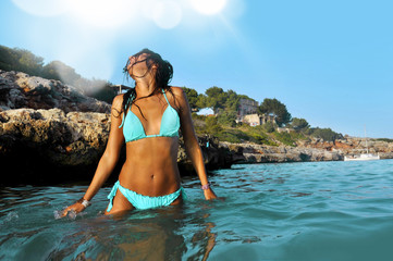 sexy woman in blue bikini at sea water enjoying summer vacation