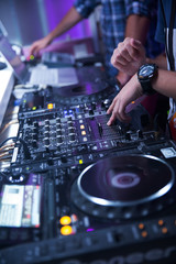 Dj mixes the track in the disco club