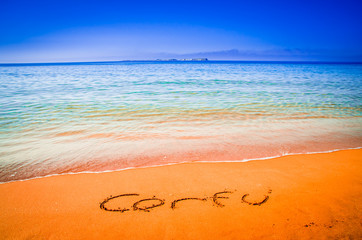 Corfu written on sandy beach in Greece. Corfu written on golden sandy beach, Greece. Selective focus.