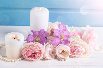 Fresh pink roses  and violet clematis flowers and candles
