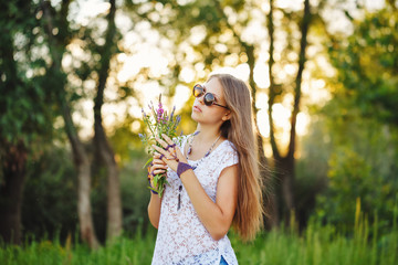 Teen Girl Boho with bouquet of wild flowers and sunglasses.