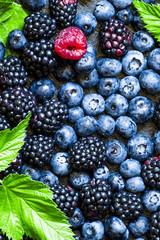 Blackberries, blueberries and raspberries with leaves on a dark