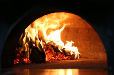 Traditional pizza in oven at restaurant kitchen