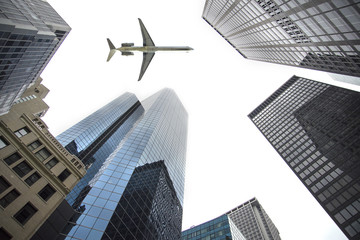 plane flying between skyscrapers