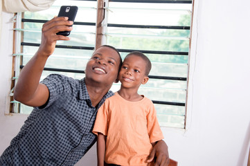 Father and  son taking pictures with his phone.