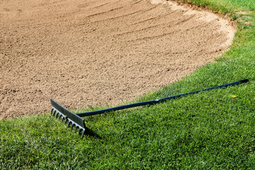 Rake on the edge of a golf course sand trap