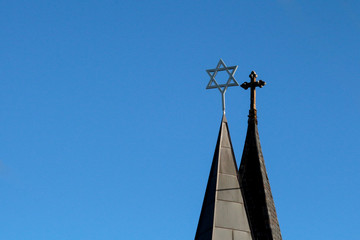 Side by side perspective of a cross and Magen David on spires