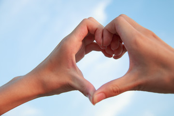 Heart-shaped hand against the sky