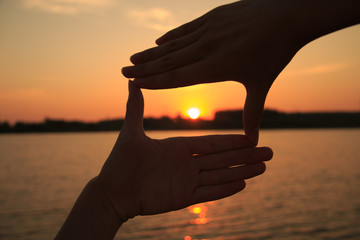 Hand frame against the sunset