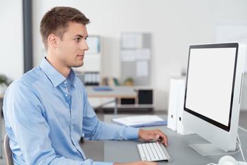 kaufmann im büro schaut auf computer
