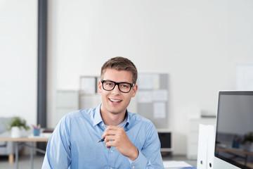 motivierter junger mann am arbeitsplatz im büro
