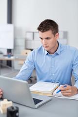 junger mann lernt mit laptop und unterlagen