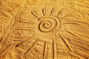 Drawing of a sun symbol on the golden sand at the seashore