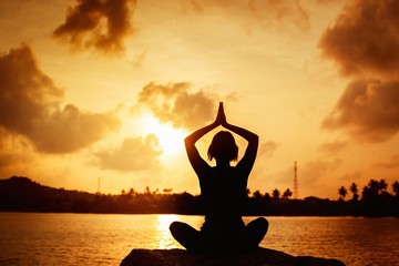 A girl is meditating on at seashore at golden sunrise