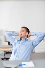 entspannter mann sitzt am schreibtisch