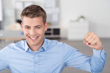 erfolgreicher mann im büro ballt die faust