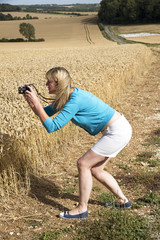 Woman using a digital camera to photograph a field of wheat
