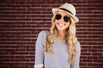 Gorgeous smiling blonde hipster with sunglasses and straw hat