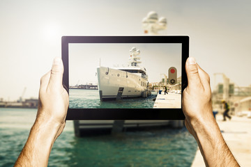 Hands holding a tablet. Taking a photo of luxury yacht docked at port. Vintage filter.