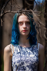 lonely blue-haired pretty girl walk in dreamy forest