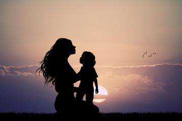 mother with son silhouette at sunset